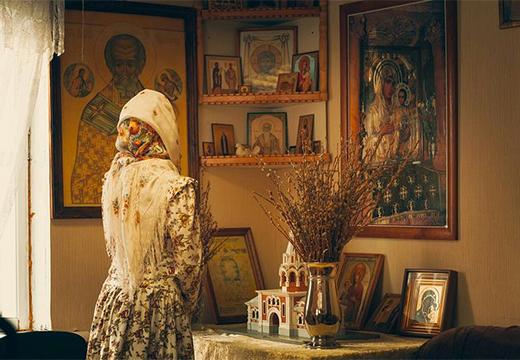 девушка молится перед иконами