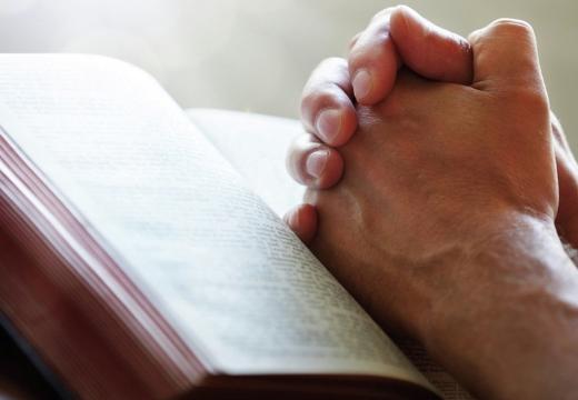 сложенные руки на книге