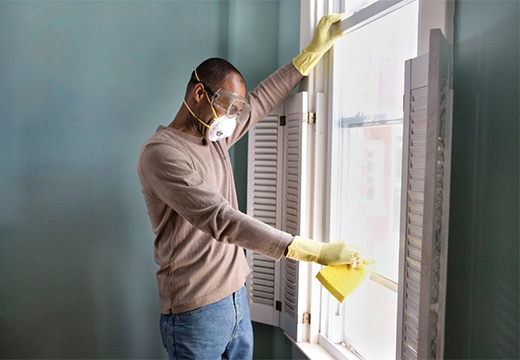 мужчина чистит окно