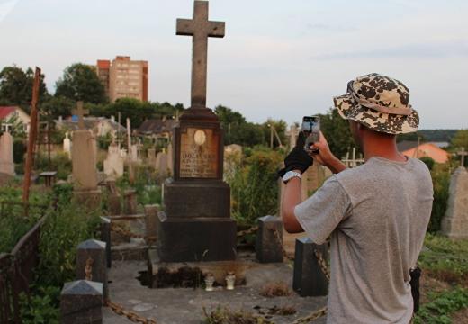 мужчина фотографирует надгробие