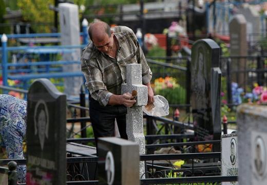 мужчина моет надгробие