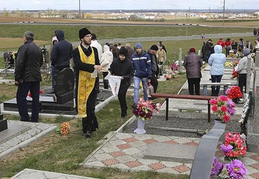 священник освящает могилы