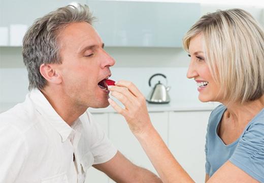 женщина угощает мужчину яблоком