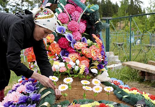 Устанавливают цветы на могилу