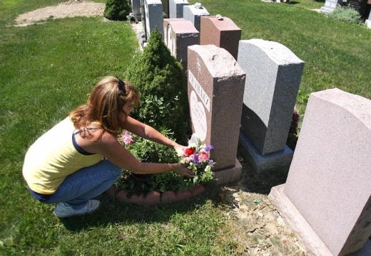 девушка ставит цветы кладбище