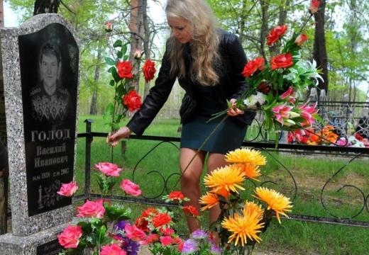 девушка украшает могилу
