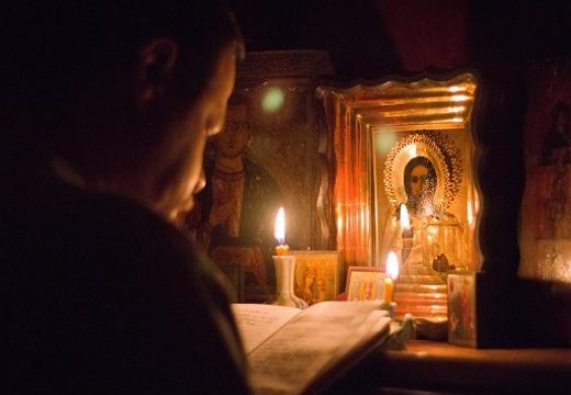 мужчина читает у икон