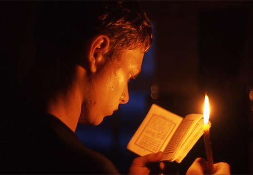 парень читает молитвослов