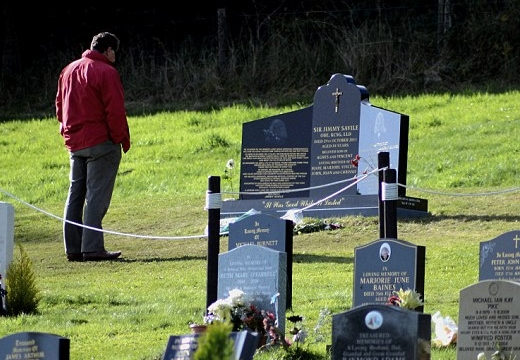 мужчина читает надгробие