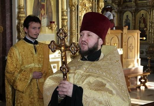 священник читает молебен