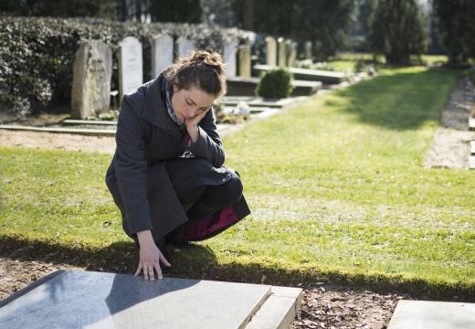 девушка читает надпись надгробия