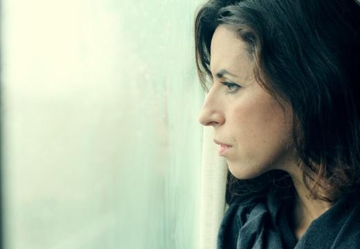 женщина грустно смотрит в окно