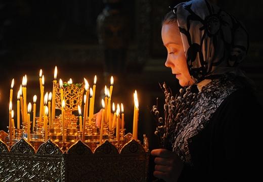 женщина ставит свечку