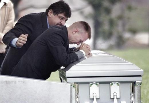 мужчина рыдает у гроба
