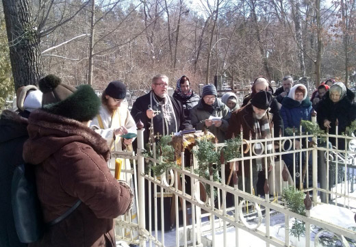 люди молятся на кладбище