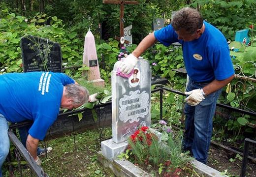 мужчины чистят могильный памятник